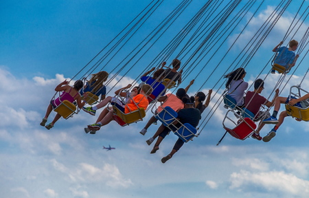 turnabout: CHICAGO, IL, July 02, 2017: Children  ride the  wave swinger, at Navy Pier, which attracts more than nine million visitors each year.