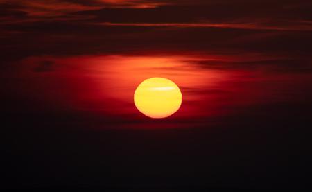 Dark sunset and the orange sun on the sky 版權商用圖片