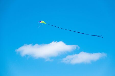 Child's toy kite flying in a clear blue sky