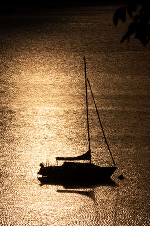 Silhouette of a sailing boat floating on a lake 免版税图像