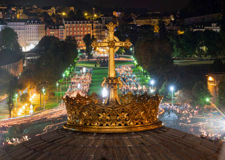 LOURDES, FRANCE - SEPTEMBER 14 2019: Cross in front of the candle procession, every night in Lourdes, France, Europe