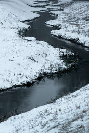 Curvy river and snowy scene in winter