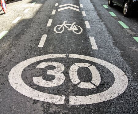 Forbidden to exceed 30 km h speed for cars and bikes in this line road photo