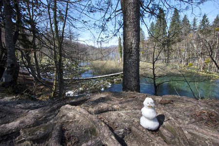 A lonely snowman melting away in spring before next winter arrives  Plitvice Lakes, Croatia photo