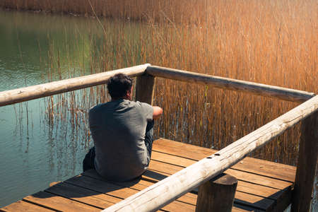 A young man alone in a lake sitting on a wooden footbridge, portrait, la arboleda, basque country