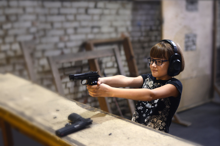 Exact hit in the purpose - girl shoots a pistol in the shooting gallery