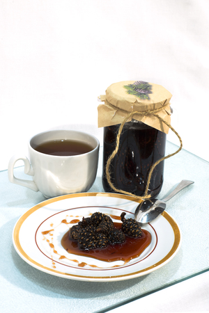 prophylactic: Jam made from pine cones on a plate and a cup of tea Stock Photo