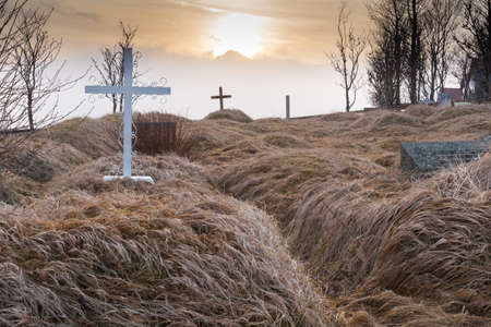 Graves in the Kálfafellsstadur Church graveyard in Iceland at sunset with crosses, headstones and long grass covering the mounds of graves