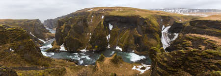 Panorama of the green cliffs and volcanic landscape of the Fjadrárgljúfur Canyon including a waterfall