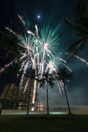 New Year's fireworks at the Hilton Hawaiian Village in Honolulu, Hawaii with the beach, palm trees and a lagoon Stok Fotoğraf