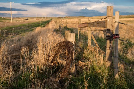 Spring thunderstorm clouds in Saskatchewan with a fencepost, roll of barbed wire, tall grass and a road in the foreground Stock Photo