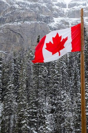 Canadian Flag waving over the mountains of Banff National Park, Canada Фото со стока
