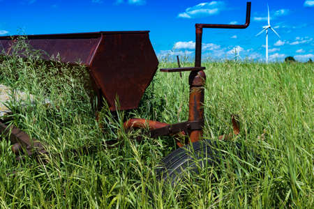 Vintage farming disc harrow in a field surrounded by tall grass with wind turbines outside of Swift Current, Saskatchewan, Canada Stok Fotoğraf - 104192298