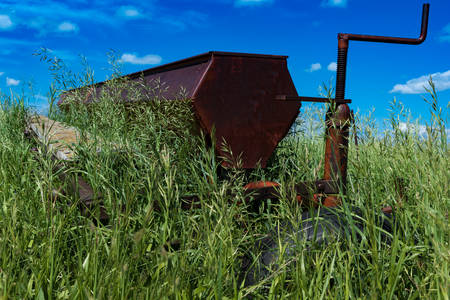 Vintage farming disc harrow in a field surrounded by tall grass outside of Swift Current, Saskatchewan, Canada Stok Fotoğraf - 104192299