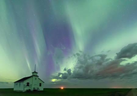 Swirl of Aurora Borealis Northern Lights over the historical North Saskatchewan Landing school established in 1914 near Kyle, Saskatchewan, Canada