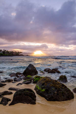 Waves breaking onto coral rocks on the shore at sunset on the north shore of Oahu, Hawaii