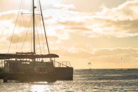 Catamaran docked on Waikiki Beach at sunset in Honolulu, Hawaii