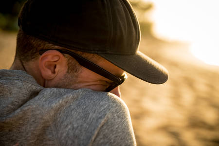 Closeup head and shoulder profile of handsome male with hat and sunglasses on beach in Hawaii