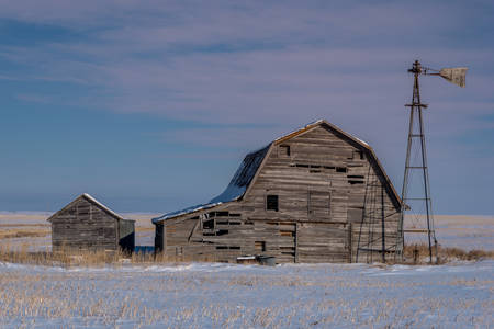 Close up of vintage barn, bins and windmill surrounded by snow under a pink sunset sky in Saskatchewan