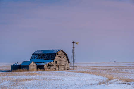 Vintage barn, bins and windmill surrounded by snow under a pink sunset sky in Saskatchewan Reklamní fotografie