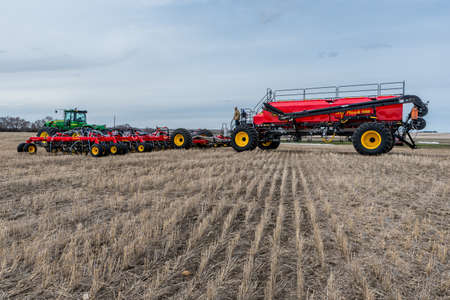 Swift Current, SK/Canada- May 4, 2019: Farmer, tractor and air drill seeding equipment in the field in Saskatchewan, Canada Stok Fotoğraf - 121921487
