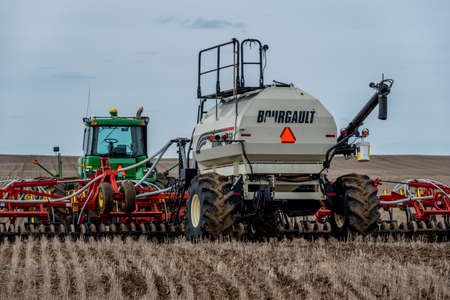 Swift Current, SK/Canada- May 4, 2019: Tractor and air drill seeding equipment in the field in Saskatchewan, Canada Stok Fotoğraf - 121921489