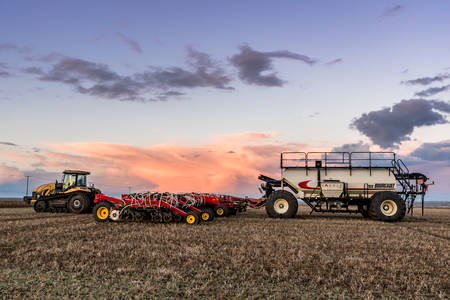 Swift Current, SKCanada- May 10, 2019: Caterpillar tractor and Bourgault air drill seeding equipment in the field in Saskatchewan, Canada Editöryel