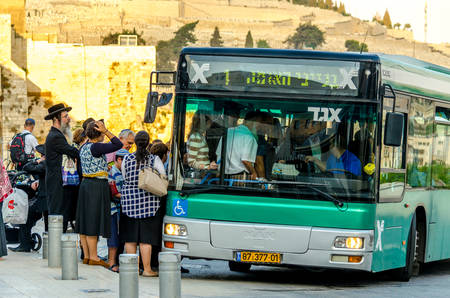 Jerusalem/Israel- August 17, 2016: Group of orthodox Jews waiting to get on a public transit bus at the Dung Gate bus stop in the Old City of Jerusalem, Israel