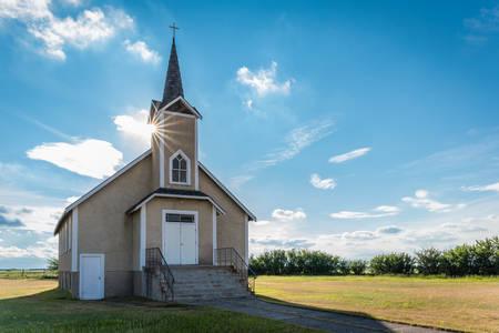 Sunburst over the steeple of the historic Nordland Lutheran Church on the prairies near Stewart Valley, Saskatchewan, Canada