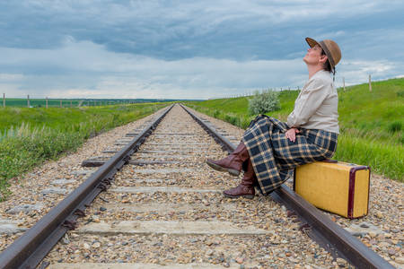 Young woman in historic dress sitting on vintage suitcase on railroad track with head back and eyes closed- journey concept
