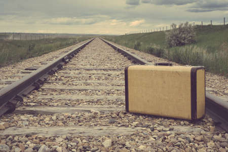 Vintage suitcase in the middle of railroad tracks on the prairies Standard-Bild