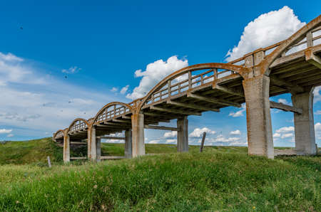 The old lichen-covered concrete bridge in Scotsguard, SK  with green grass in foreground Stok Fotoğraf