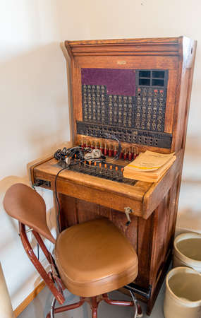 Antique telephone switchboard with chair and telephone directory Archivio Fotografico