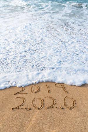 2019 2020 scritto nella sabbia con un'onda che cancella il concetto di Capodanno 2019 Archivio Fotografico