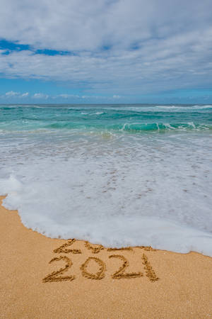 2020 2021 written in the sand with a wave washing away 2020- New Year's concept Archivio Fotografico