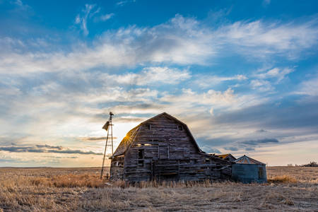 Sunset over a vintage wooden barn, bins and windmill in a Saskatchewan, Canada Banque d'images
