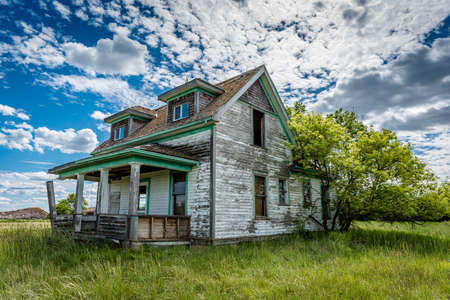 Old, abandoned prairie farmhouse with trees, grass and blue sky in Saskatchewan, Canada Stock Photo
