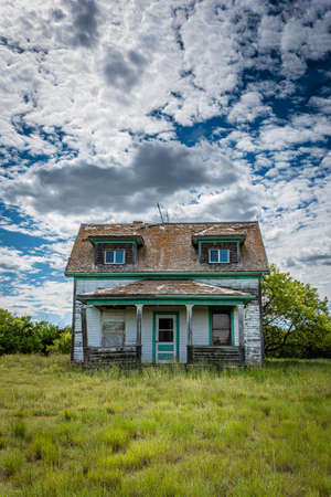 Old, abandoned prairie farmhouse with trees, grass and blue sky in Saskatchewan, Canada