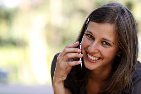 Happy young lady talking on mobile phone Stock Photo