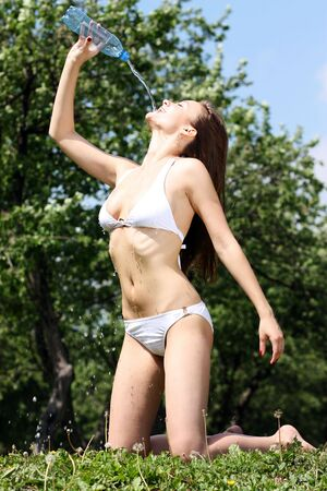 Heat. The young woman drinks mineral water  photo