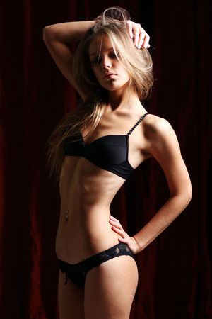 Sexy blond in black lingerie over dark background  photo