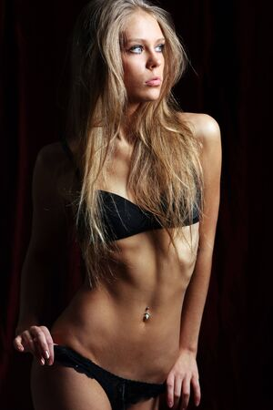 Sexy blond in black lingerie over dark background  Stock Photo