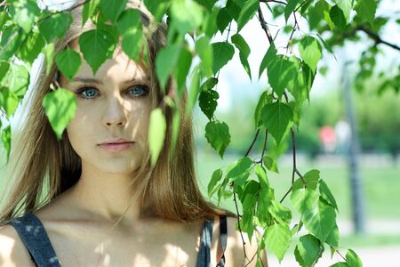 Portrait of the young beautiful girl on a background of leaves of a birch  photo