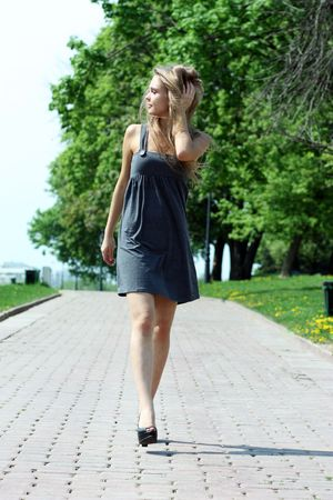 young beautiful girl walks in outdoor photo