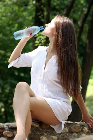 wet lips: Heat. The young woman drinks mineral water  Stock Photo