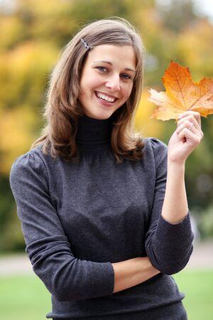 18's: Beautiful romantic brunette with golden autumn leaf