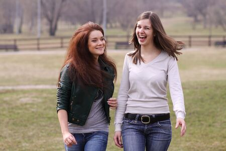 Two cheerful walking girls in the park photo