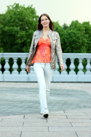 Full length, walking woman in blue jeans photo