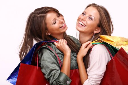 elation: Twins sisters holding shopping bags on white isolated