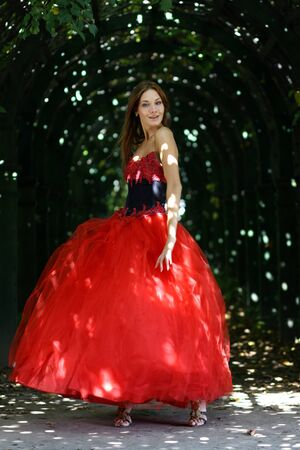 Beautiful woman in a red dress walking in alleyway in park  photo